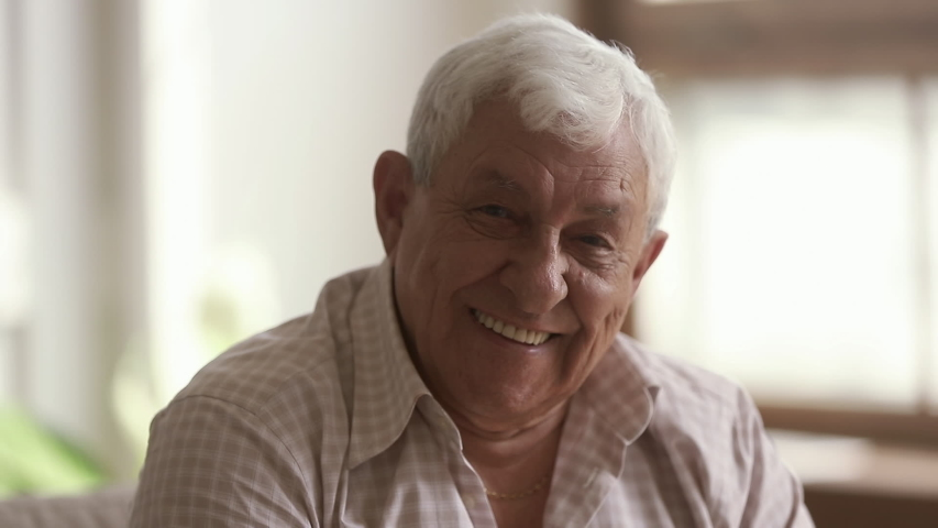 Senior old gray-haired man looking at camera, serious happy elder mature grandfather with toothy smile posing for close up video portrait alone at home or retirement house, older people health care