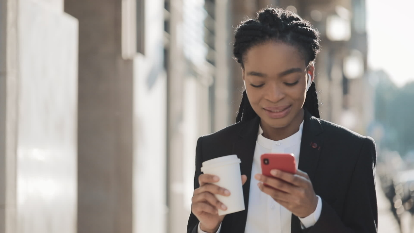 Young African American businesswoman in a suit Woman using a smartphone voice recognition function online drinking coffee walking on a city street on a summer day. | Shutterstock HD Video #1032304271