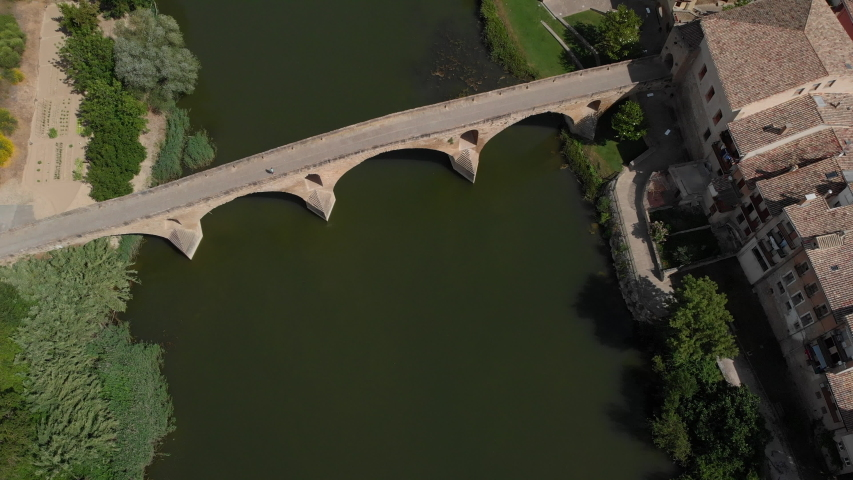 Aerial view of Puente La Reina, Spanish village along Camino de Santiago or Way of Saint James. Urban landscape with bridge and river in Navarre region, Spain seen from drone flying in sky | Shutterstock HD Video #1032444521