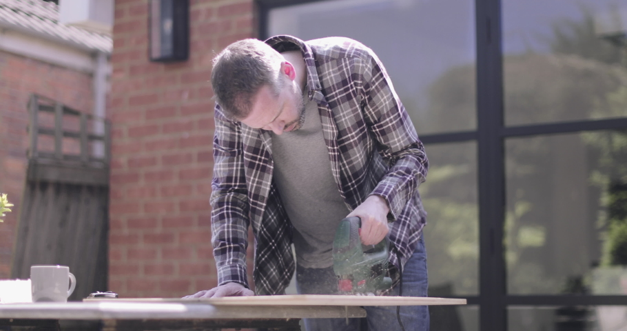 Adult man doing carpentry DIY at home in garden | Shutterstock HD Video #1032446831