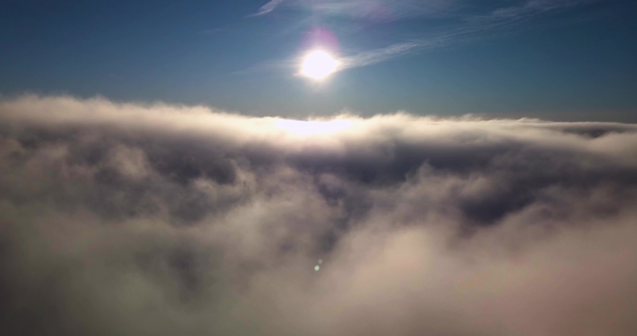 Flying over thick fog andclouds in the sunlight with blue sky, 4k aerial video | Shutterstock HD Video #1032464321
