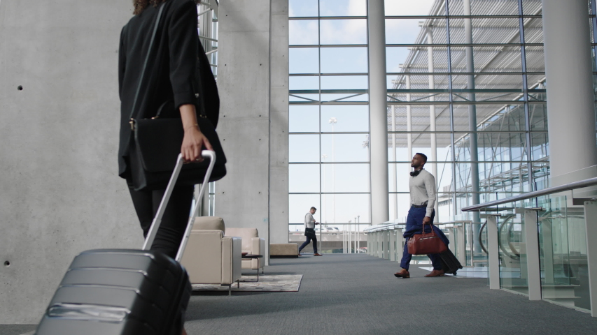 Diverse people at busy airport pulling trolley bags arriving and departing terminal tourists travelling international walking in lobby with luggage on the move 4k footage | Shutterstock HD Video #1032465131