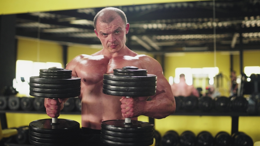 Lifting dumbbells for bigger biceps close up. Close up handsome man with big biceps lifting weights   Shutterstock HD Video #1032475811