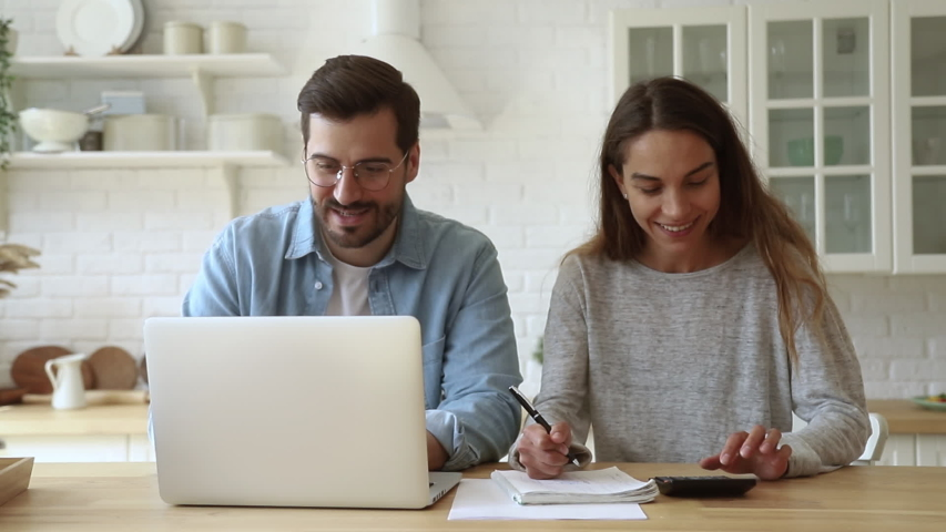 Happy young husband and wife using calculator laptop computer talking doing paperwork together sit at kitchen table discussing family mortgage loan payments pay bills manage finances expenses at home | Shutterstock HD Video #1032517241