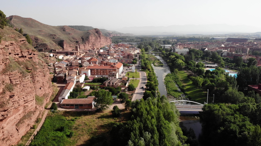 Aerial view of Najera, small Spanish village in Spain along Camino de Santiago or Way of St. James. Urban landscape and river Najerilla seen from drone flying in sky | Shutterstock HD Video #1032518351