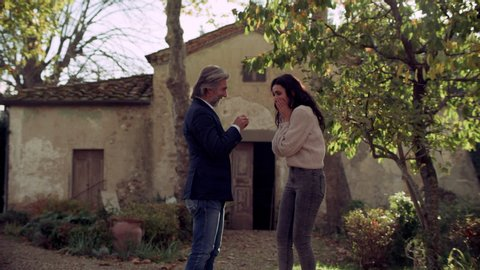 Italian man proposes with an engagement ring to his girlfriend in a beautiful yard in Tuscany. 4k RED.