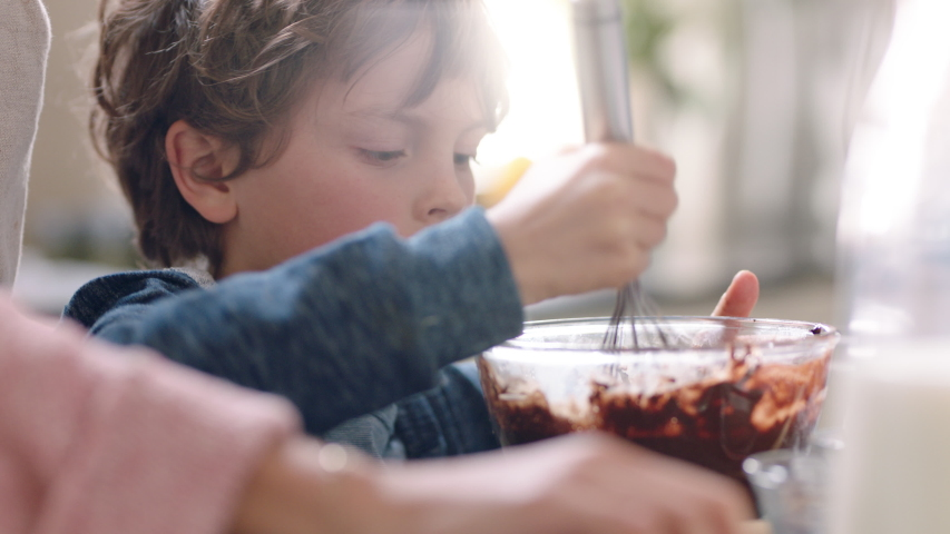 Happy little boy helping mother bake in kitchen mixing ingredients baking chocolate cupcakes preparing recipe at home | Shutterstock HD Video #1032607391