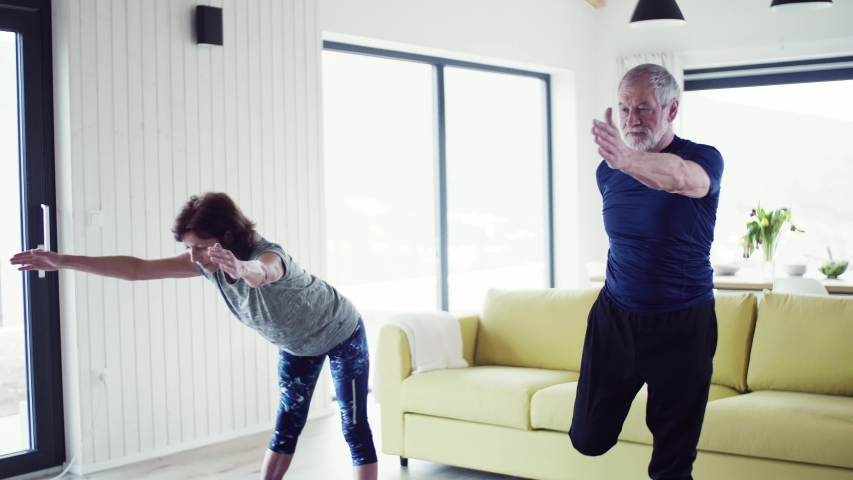 A senior couple indoors at home, doing exercise indoors. | Shutterstock HD Video #1032675701