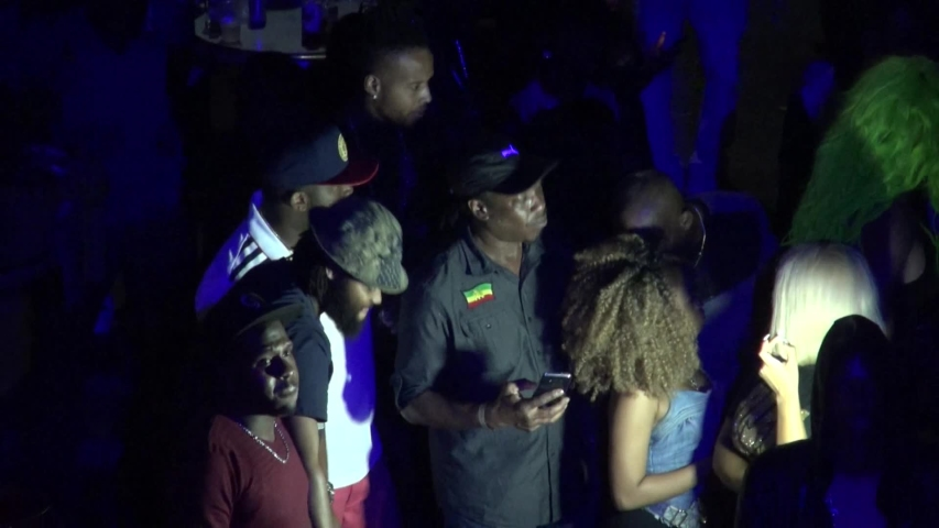 KINGSTON, JAMAICA - CIRCA JUNE 2017 : Scenery of outdoor street night club. Man and woman enjoying dance, popular night life for many Jamaican people. Reggae and hip hop music are played by DJ. | Shutterstock HD Video #1032767951