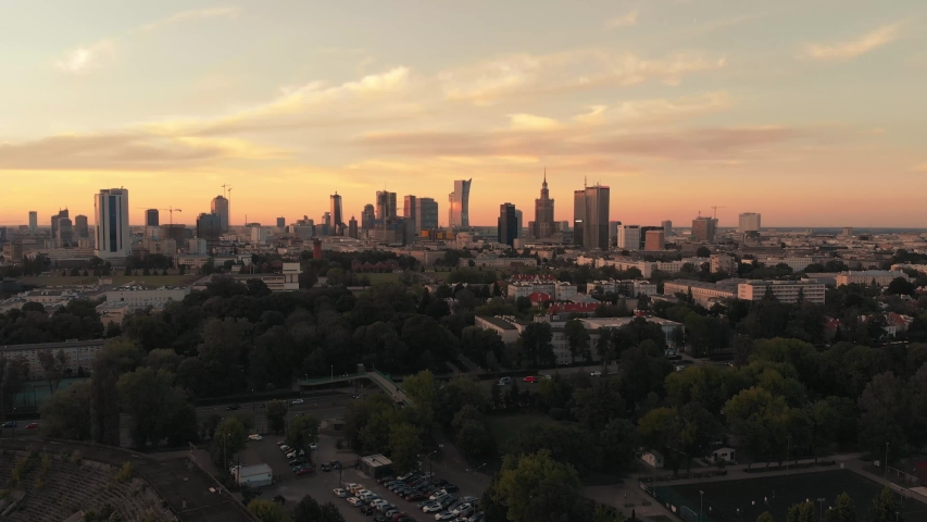 Establishing aerial shot of Warsaw city center in the evening. Dusk with the orange sky. View from above. Poland. | Shutterstock HD Video #1032768071