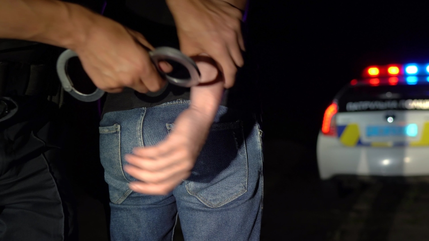 Police officer puts handcuffs on arrested man at night and leads him to a police car