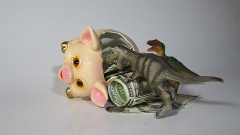 Two carnivorous dinosaurs T Rex and VelociRaptor killed a pig coin box and ate its insides capital, Finance in the pig year 2019. Allegory