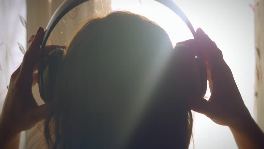 Young girl wears headphones listening to music in headphones looks at the window and sunlight rays