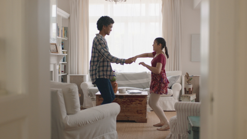 happy father and daughter dancing at home teenage girl having fun dance with dad celebrating weekend together 4k footage #1032899441