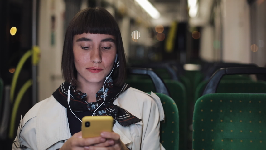 Young stylish woman in headphones listening to music and browsing on mobile phone riding in public transport. City lights background. | Shutterstock HD Video #1032944441