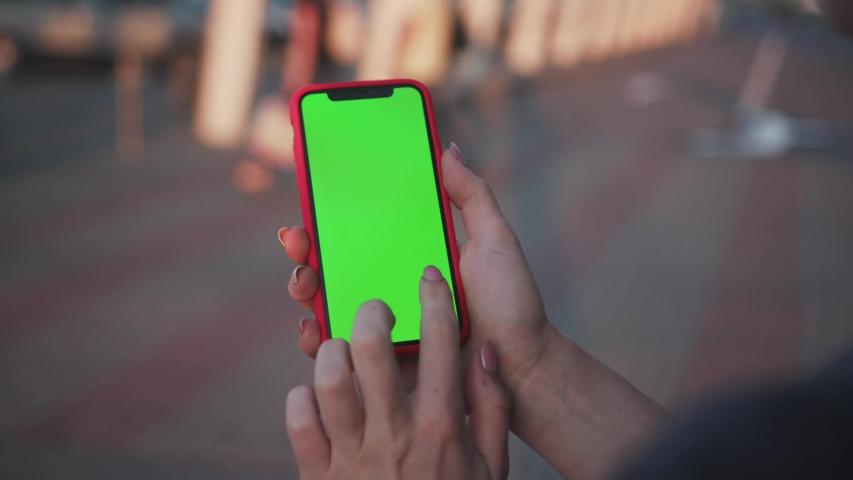 Close-up young sociable woman using a smartphone outdoors. first-person view of female hand holding greenscreen gadget and browsing social networks. | Shutterstock HD Video #1032966791