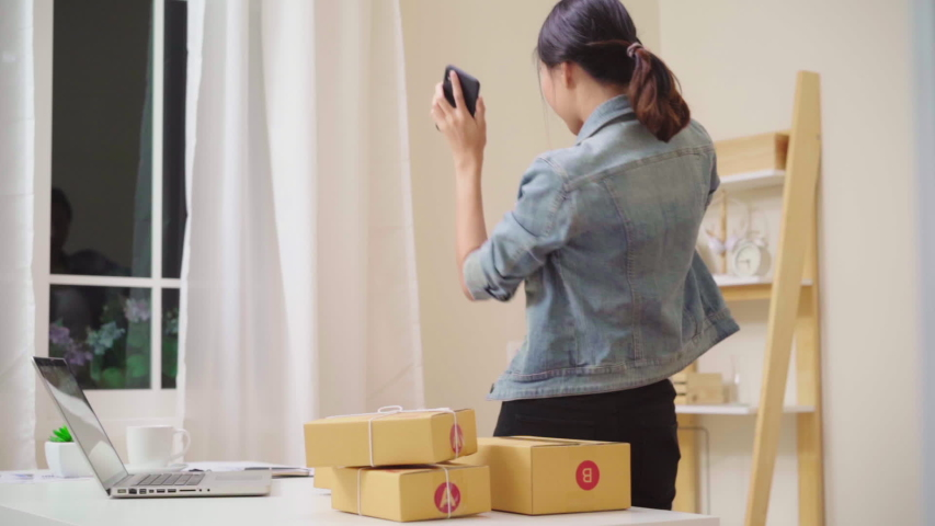 Asian young woman checking product on stock and save to laptop working at house. female entrepreneur business owner of SME happy dancing according rhythm song, relax after work at home. Slow motion. | Shutterstock HD Video #1033046981