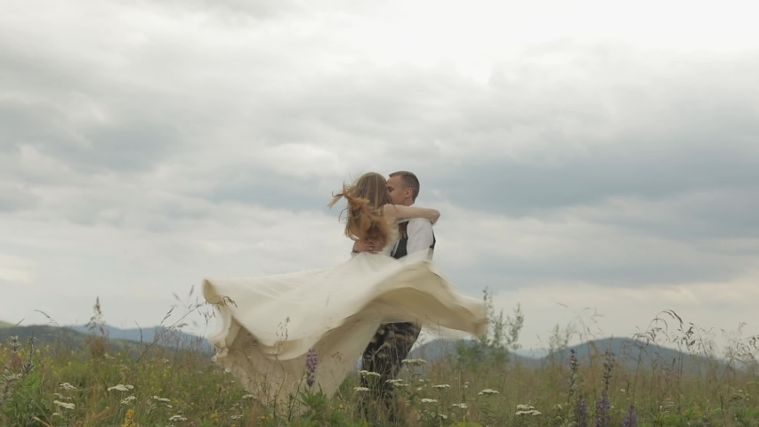 The groom runs for the bride on a mountain hills. Wedding couple. Happy family. Man and woman in love. Lovely groom and bride. Wedding day. Slow motion