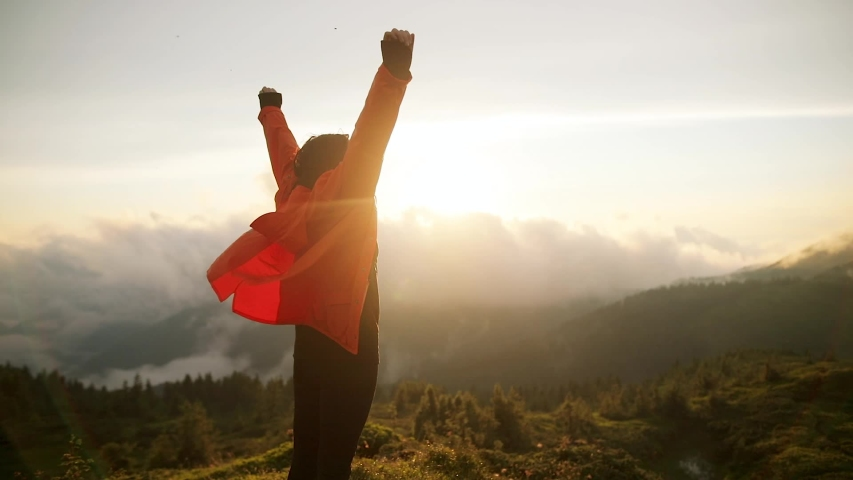 Camera follows hipster millennial young woman in orange jacket running up on top of mountain summit at sunset, jumps on top of rocks, raises arms into air, happy and drunk on life, youth and happiness | Shutterstock HD Video #1033184651