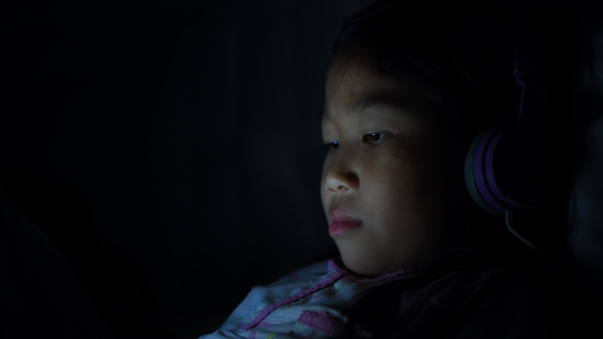 Night shoot: Little child playing smartphone lying on bed, light and the blue light has a negative effect on the child's eyes. Health care concept  | Shutterstock HD Video #1033206941