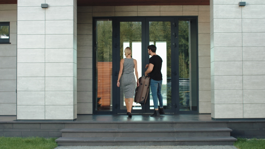 Traveler couple entering hotel back view. Elegant woman and going up stairs in hotel man with luggage. Back view of couple entering luxury hotel residence. Modern couple coming home with bag