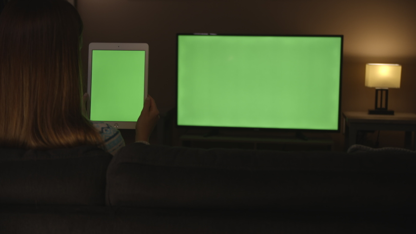 Woman watching green screen tablet and tv in evening, 4k #1033241471