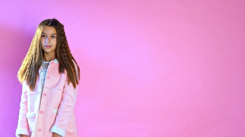 Beautiful fashionable girl poses on a pink background | Shutterstock HD Video #1033248851
