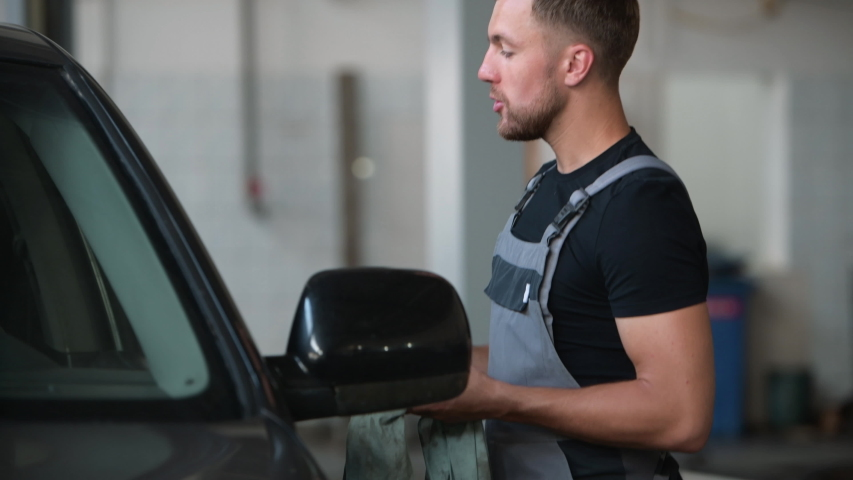Have conversation. Young mechanic stands indoors near black car. After repairing automobile. | Shutterstock HD Video #1033269161