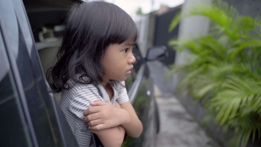 Moody child having to go home after the holiday looked out the car window | Shutterstock HD Video #1033271051