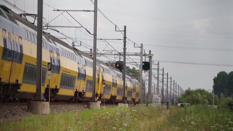 Dutch Double Decker train passes in high speed near Hilversum and Utrecht on a sunny day