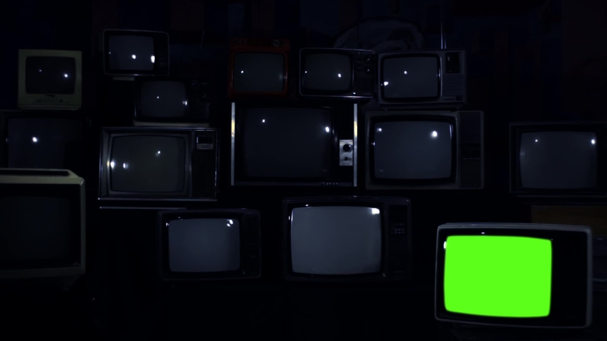 """Pile of Retro TVs from 80s and One TV Turning On Green Screen. Dark Blue Tone. Zoom In. You can replace green screen with the footage or picture you want with """"Keying"""" effect (check out tutorials). 
