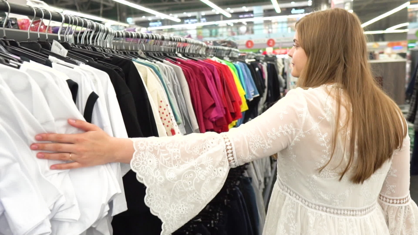 Close up of a girl goes through clothes dresses summer outfit, T-shirts and shirts and shop the boutique, the supermarket on the rack, close-up of hands and racks of clothes, shopping    Shutterstock HD Video #1033444091