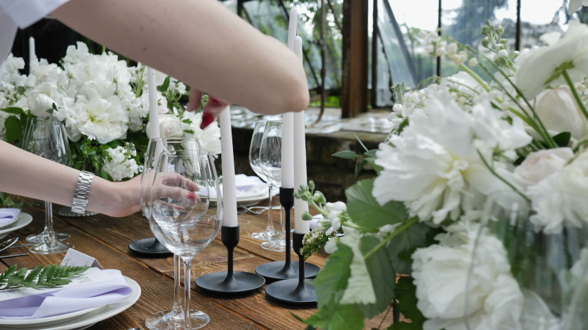 Decorating a Festive table. Wedding Table Decoration with Bouquets of Natural Fresh Flowers for a Family Feast | Shutterstock HD Video #1033490771