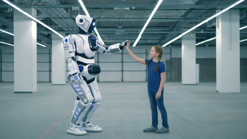 Droid and girl touch hands, side view. School kid, education, science class concept. | Shutterstock HD Video #1033569701