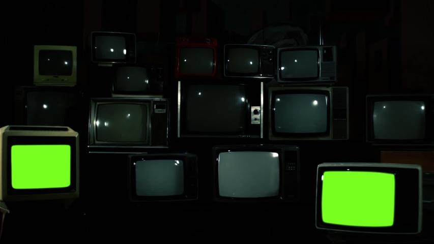 Two Retro TV Turning On Green Screen over a Pile of Retro TVS from the 80s and 90s. Blue Steel Tone. | Shutterstock HD Video #1033573541