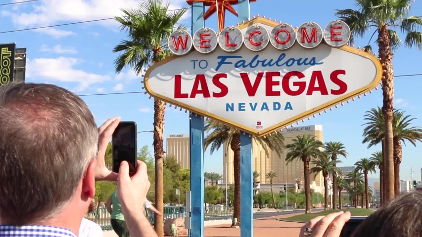 Las Vegas, Nevada / United States - 07 02 2019: Man taking picture of Las Vegas sign with tourists underneath posing for picture | Shutterstock HD Video #1033655351