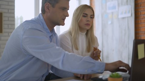 Male mentor or executive manager boss teaching female intern explaining online work pointing at computer screen, team leader supervisor training new worker instructing about pc software in office 4K