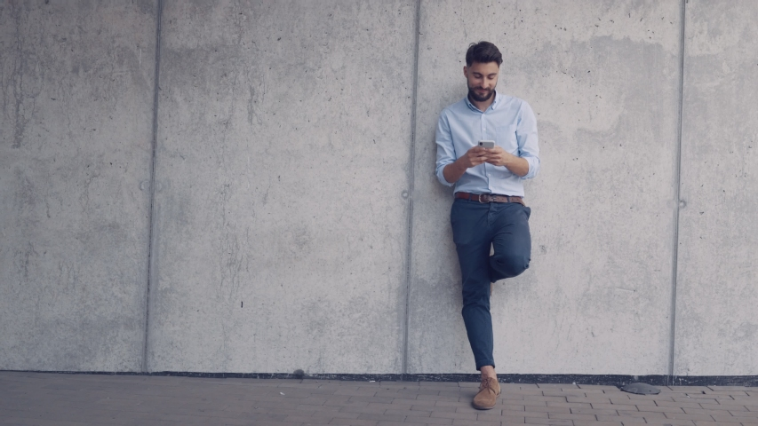 Smiling young man leaning against wall and texting on smartphone #1033840301