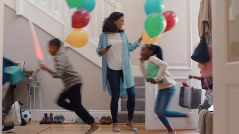 funny birthday party mother opening door with happy children running in house with balloons excited for celebration 4k