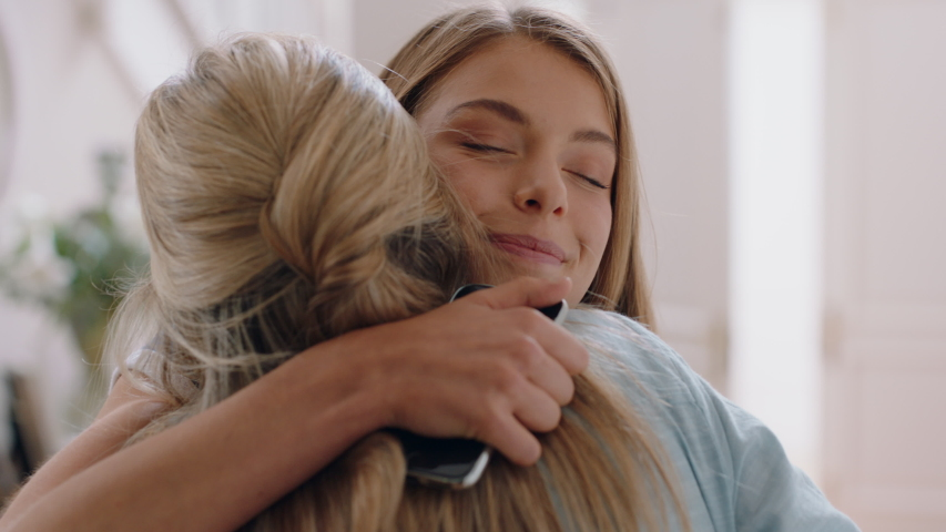 Beautiful teenage girl hugging mother congratulating daughter successful achievement excited mom feeling proud parent enjoying family connection at home 4k footage