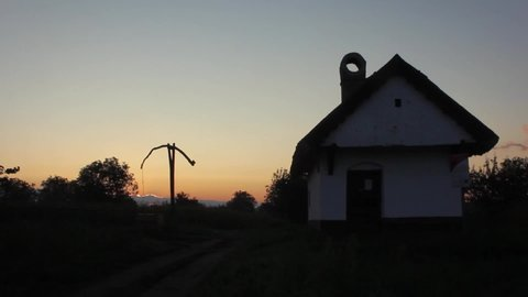 Still timelapse of a shadoof and a small house in the colorful sunrise.