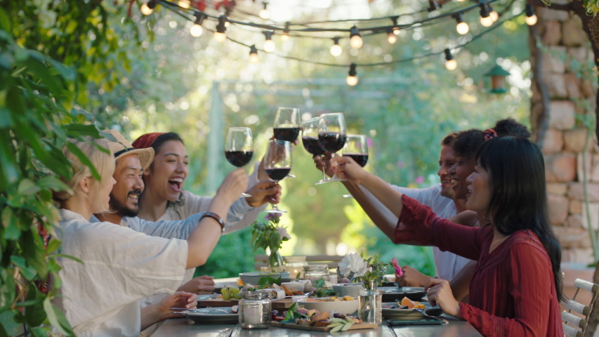 Friends making toast celebrating dinner party drinking wine eating mediterranean food sitting at table enjoying beautiful summer day outdoors 4k footage