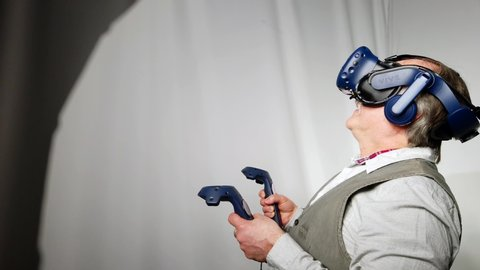 Montreal, quebec / canada - 04 12 2019: an old man uses htc vive vr headset  and controllers for virtual reality game arcade center montvr brossard