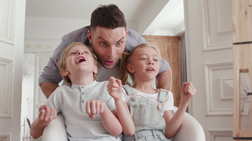 Active Family Group Moves in Large Flat or Real Estate. Playful Dad with Beautiful Small Child. Positive Looking at Casual Relocating or Unpacking. Two Little Babies Ride a Chair near Carton Package | Shutterstock HD Video #1034046731