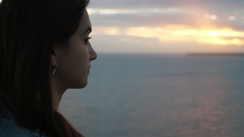 Amazing profile of a beautiful brunette girl with waving hair looking at  the Black Sea waves and thinking about her boyfriend at sunset in summer in slo-mo   #1034083391