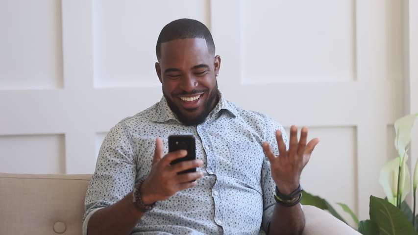 Surprised excited black man winner hold smartphone read good internet news amazed by mobile online bet bid game win, happy african guy look at cell phone screen overjoyed by victory success at home | Shutterstock HD Video #1034099171