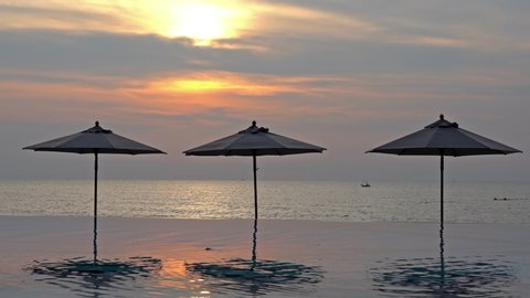Parasole umbrellas reflecting in an infinity pool at a luxury beachfront location with the tropical setting sun behind over the ocean