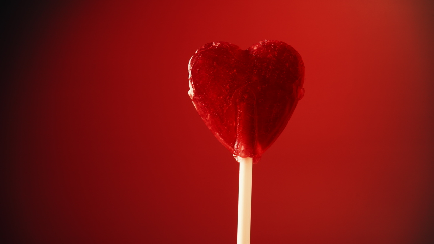 Sweet candy heart on stick against red background. Love, valentines day or charity concept | Shutterstock HD Video #1034149691