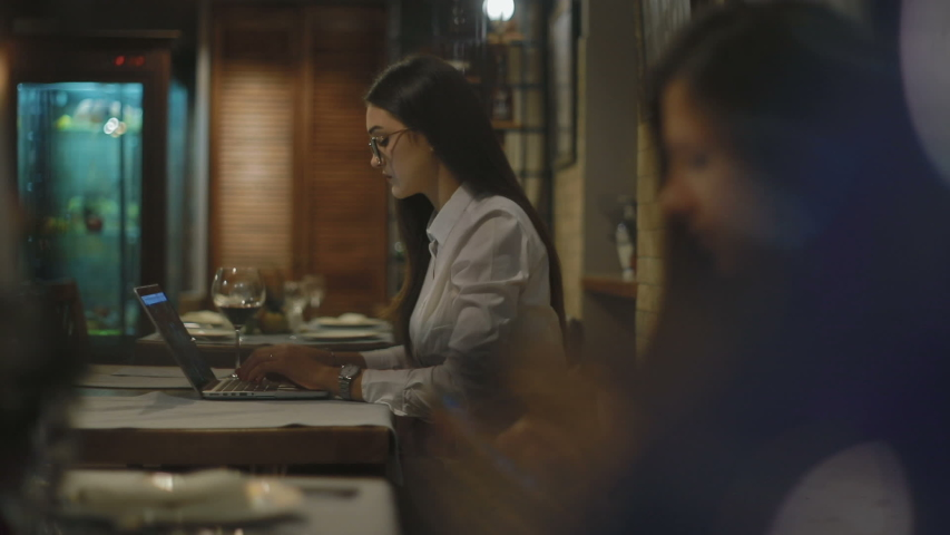 Slow motion behind soft focus brunette girl in glasses has sip of red wine at table with laptop in cafe | Shutterstock HD Video #1034156111