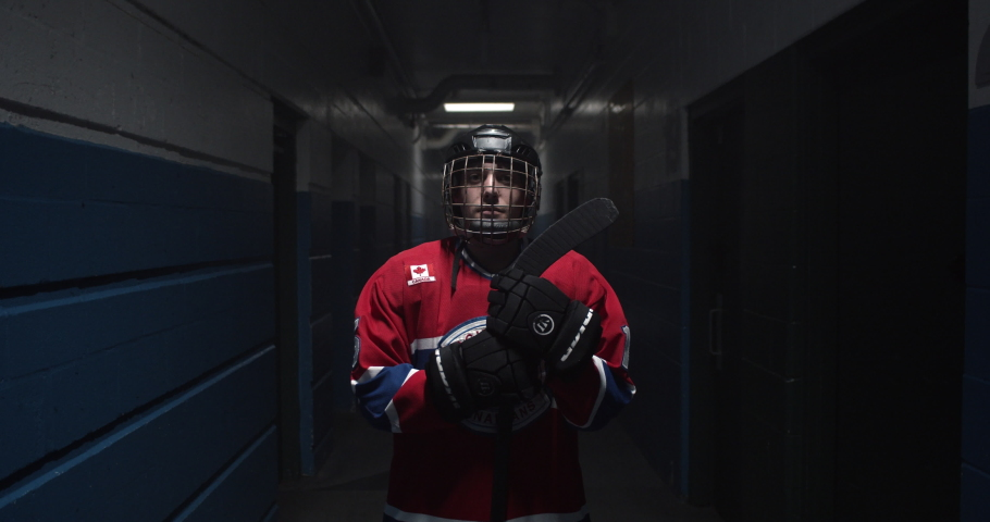 Portrait of hockey player in arena hallway holding onto his stick in full hockey attire. | Shutterstock HD Video #1034196971